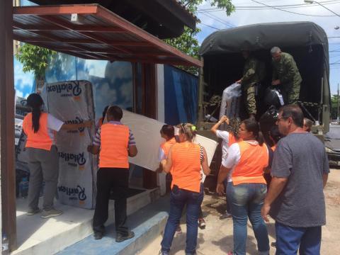 Militares e voluntários realizando a distribuição do material arrecadado em doações.