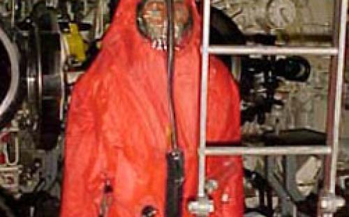 Sala de torpedos de vante com operador de armas submarinas com traje especial