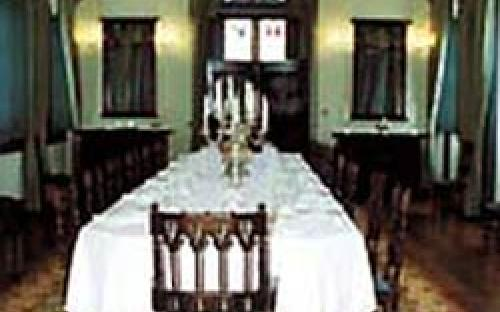 Sala de jantar, com móveis em estilo neogótico, apresentando o serviço de mesa, com castiçais e porcelanas brasionadas