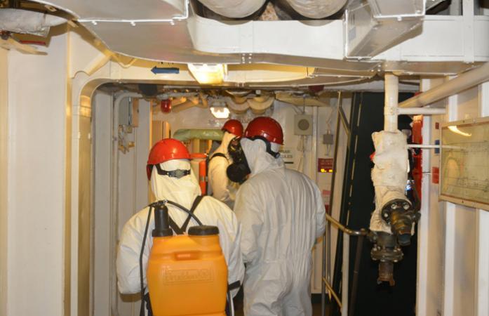 """Militares componentes da (UDVE) realizando sanitização a bordo NDM """"Bahia""""."""